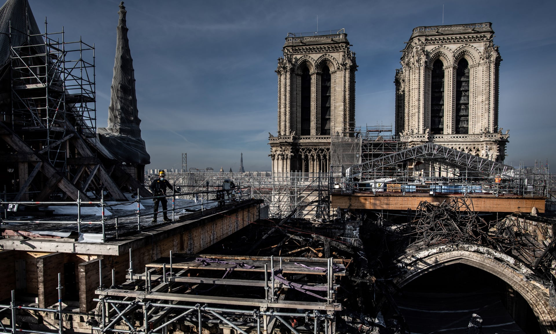 Workers on the roof of Notre Dame removing the burnt scaffolding that surrounded the spire