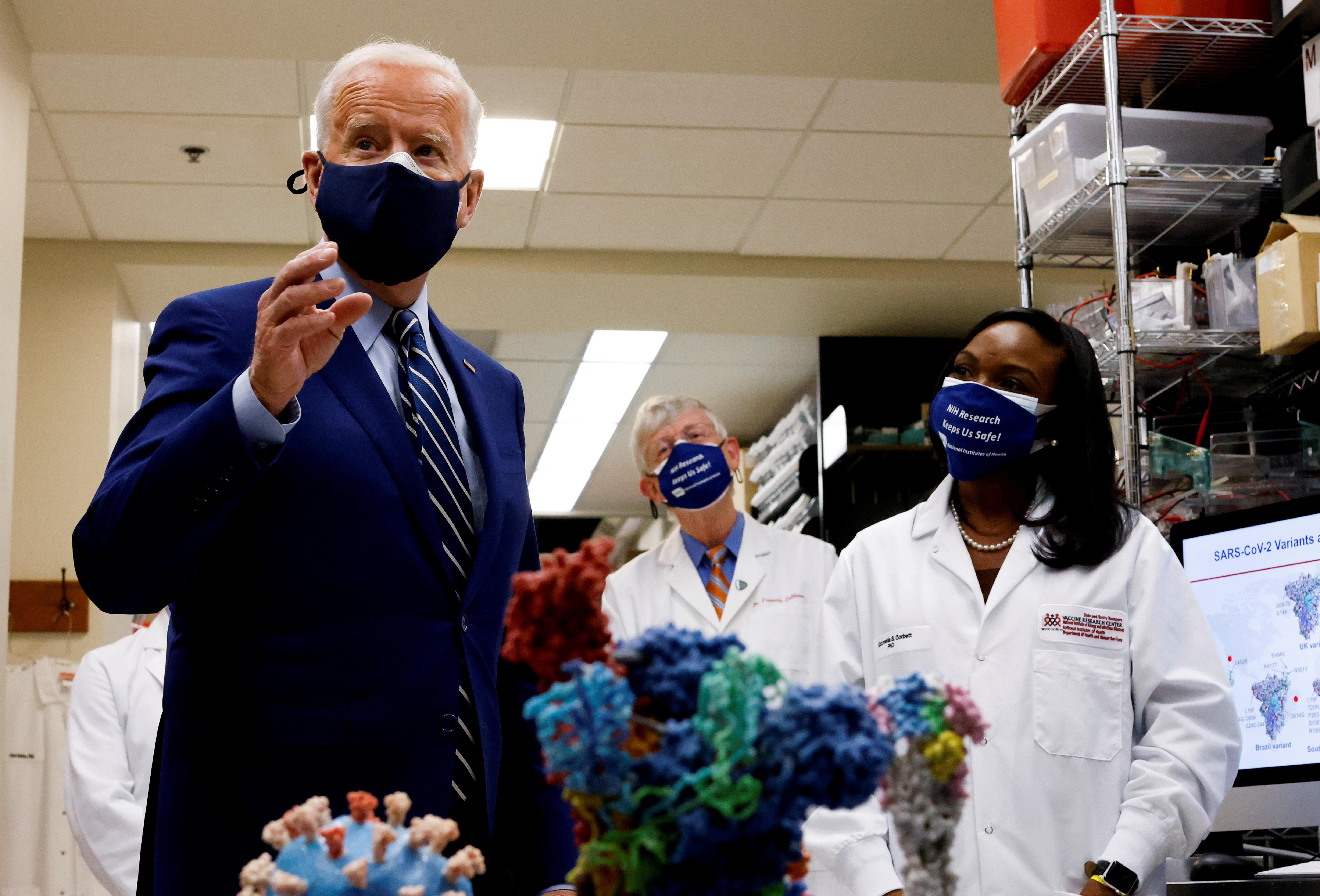U.S. President Joe Biden speaks next to an NIH staff member as NIH Director Francis Collins listens during a visit to the Viral Pathogenesis Laboratory at the National Institutes of Health (NIH) in Bethesda, Maryland, U.S., February 11, 2021.