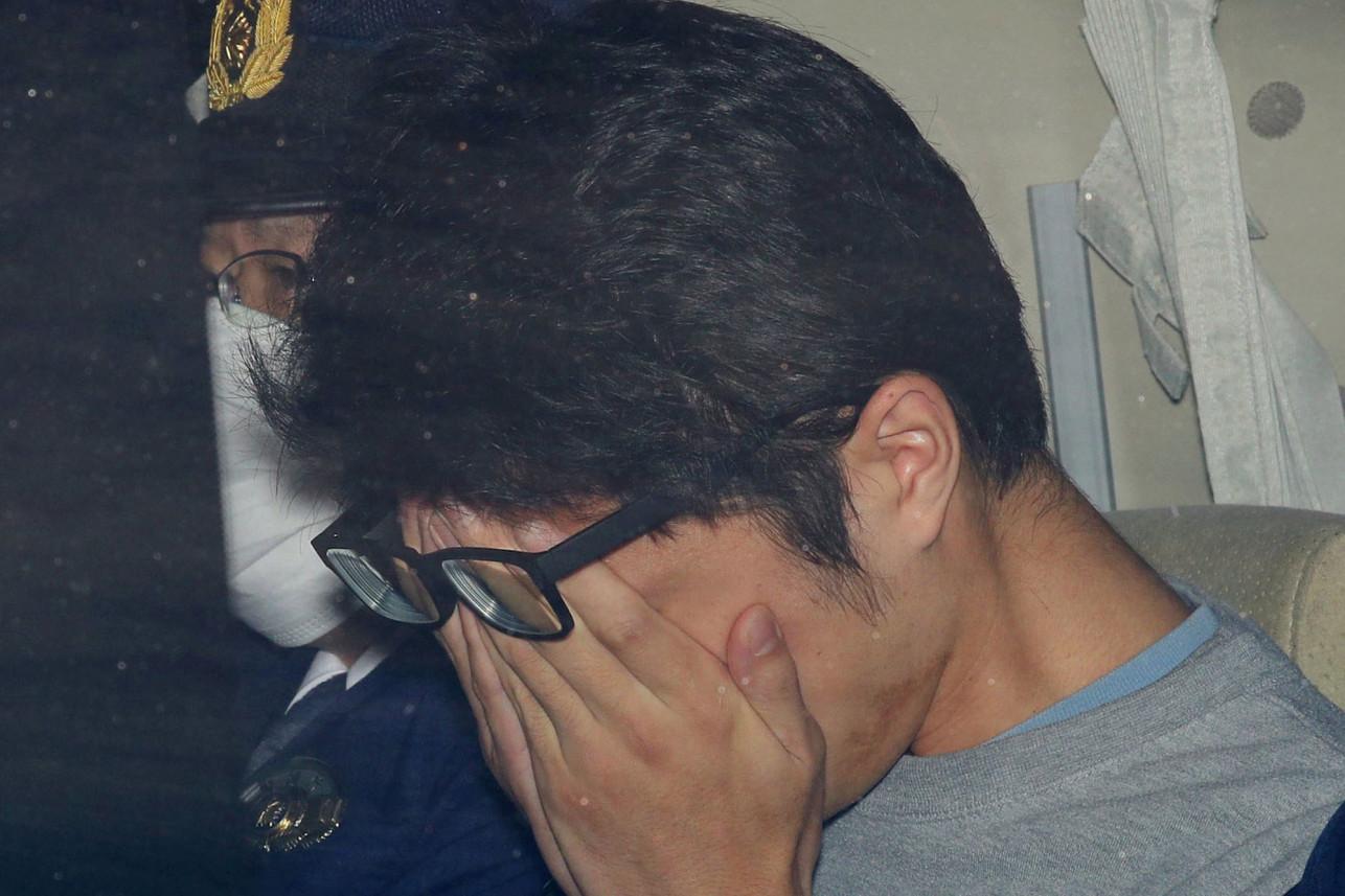 Takahiro Shiraishi covers his face inside a police car in Tokyo. Via Reuters