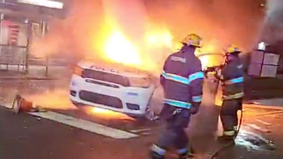 Firefighters hose down a burning police vehicle in Philadelphia, US, October 27, 2020 in this still image taken from social media video via Instagram @reef_gotcars_58. (Reuters)