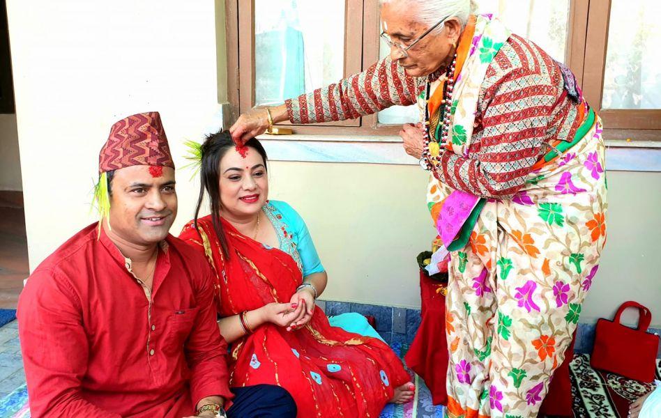 आमाको हातबाट टीका ग्रहण गर्दै हास्यब्यँग्य अभिनेता जितु नेपाल, पत्नीका साथ ।फाइल तस्वीर
